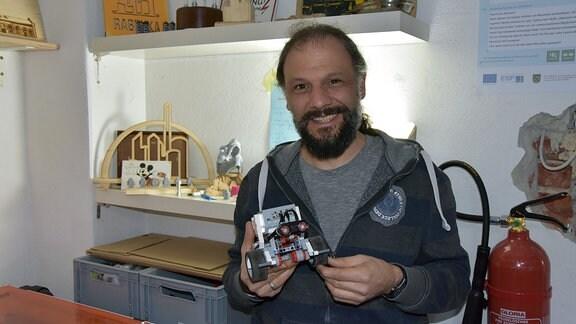 Markus Hacker mit einem von Jugendlichen gebauten Miniroboter.