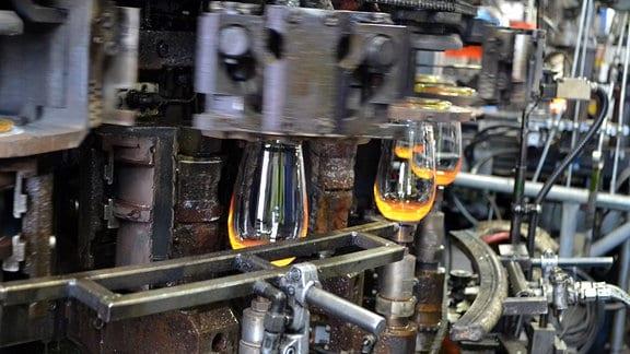 Gläser hängen in einer Maschine und glühen.