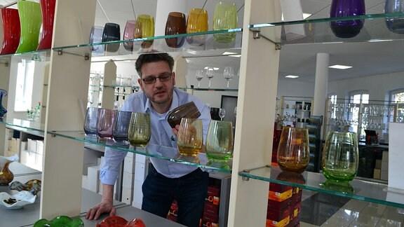 Ein Mann steht vor einem Regal mit bunten Gläsern.