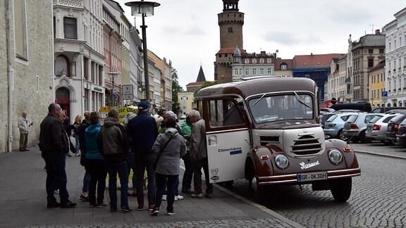 Menschen beim Einsteigen in den Oldtimer-Bus