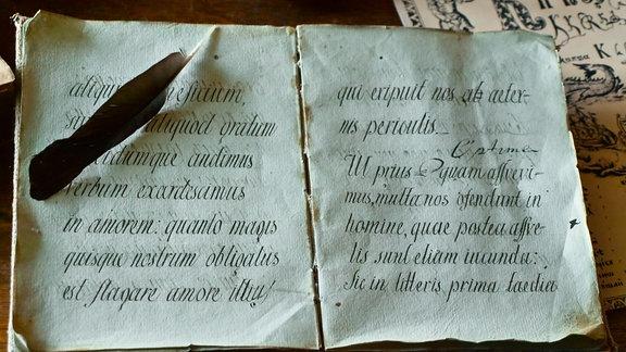 ein historisches Schriftstsück mit einem federkiel daneben