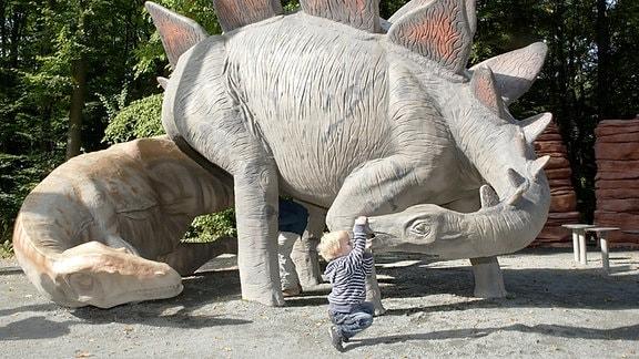 Allosaurus (links) und Stegosaurus (rechts) mit Kind am Maul.