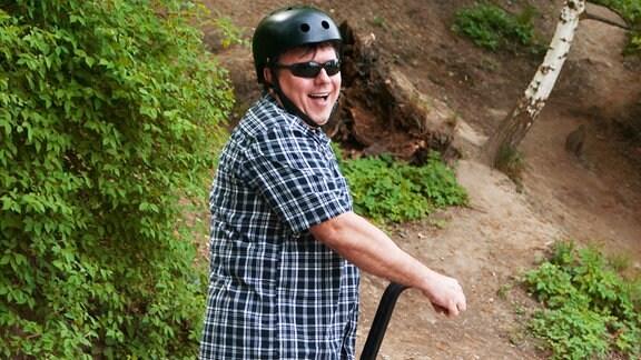 Ein Mann steht lachend auf einem Segway.
