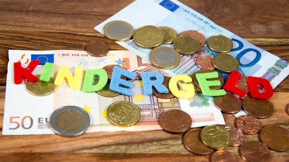 Geldscheine, Münzen und Buchstaben, die das Wort Kindergeld ergeben, auf einem Tisch