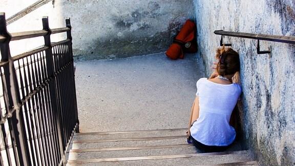 Angelehnt an die Wand sitzt eine junge Frau auf einer Treppe