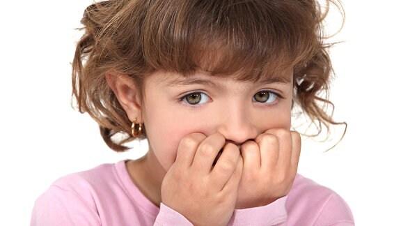 Ein kleines Mädchen blickt ängstlich mit vor den Mund gehaltenen Händen