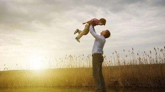 Mann hebt Kind vor Sonnenuntergang in die Luft