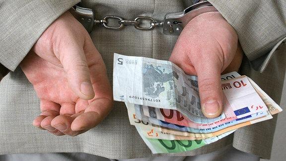 Geschaeftsmann in Handschellen haelt Geldscheine in einer Hand.