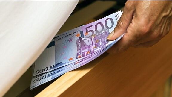 Ein Mensch versteckt mehrere 500 Euro Scheine unter einer Matratze.