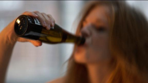 Eine junge Frau trinkt eine Flasche Bier.