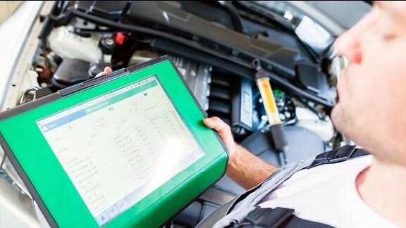 Ein Mann liest mit Hilfe eines Computers Autodaten aus.