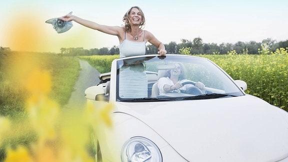 Sommerausfahrt mit Beetle Cabrio - Eine Frau schwenkt ihren Hut.