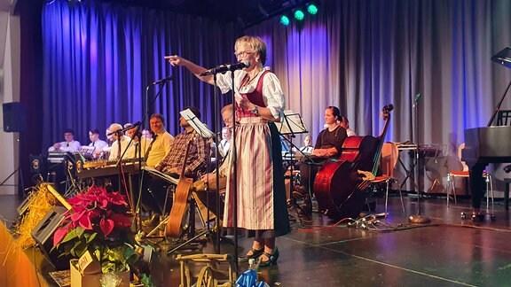 Carmen Krüger vom Erzgebirgsverein steht im Trachtenkleid auf der Bühne und verkündet das Wort des Jahres