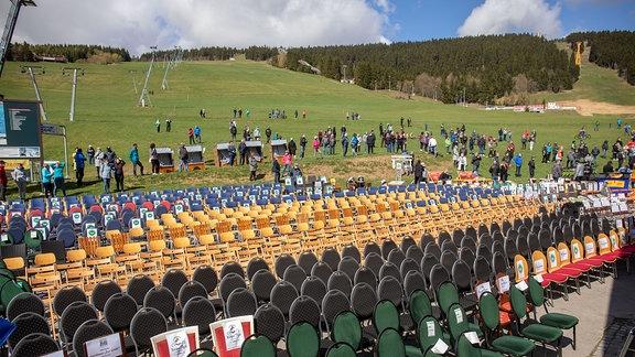 Am Fuße eines grasbewachsenen Skihangs am Fichtelberg stehen zahlreiche Stühle und einige Strandkörbe
