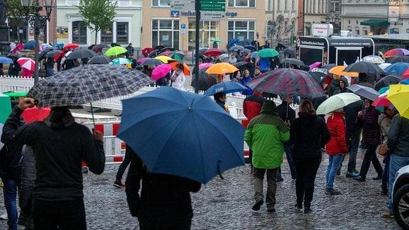 Auf dem Marktplatz von Annaberg-Buchholz stehen Menschen mit Regenschirmen in der Hand