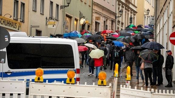 Menschen mit Regenschirmen laufen in Annaberg-Buchholz eine Straße entlang. Im Vordergrund steht ein Polizeifahrzeug