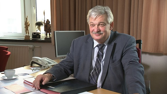 Der Oberbürgermeister von Aue, Heinrich Kohl, sitzt an einem Schreibtisch.