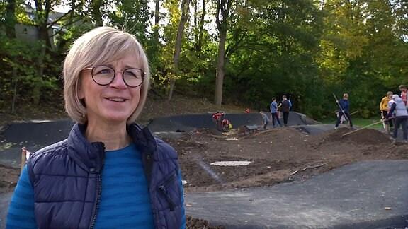 Eine blonde Frau mit Brille (Ehrenfriedersdorfs Bürgermeistern Silke Franzl) steht vor einer Baustelle
