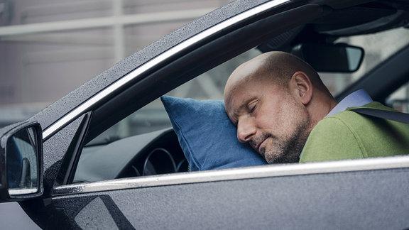 Ein Mann schläft im Auto