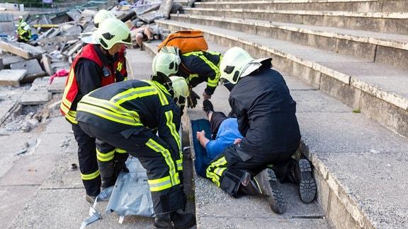 Feuerwehrleute und DRK-Helfer versorgen einen Verletzten auf der Tribüne