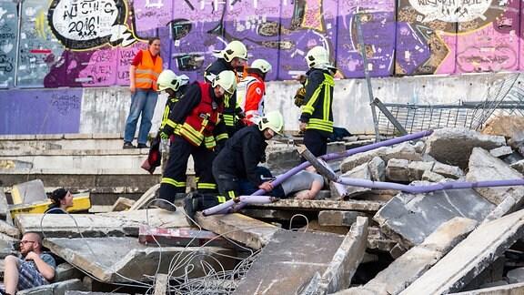 Sechs Feuerwehrleute und DRK-Helfer bergen einen Verletzten auf der Tribüne