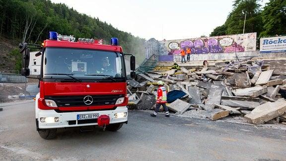 Ein Feuerwehrauto fährt an der eingestürzten Tribüne vorbei