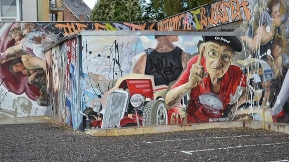 """Straßenkunst des Künstlers """"Tasso"""" in Zwickau: Eine alte Frau mit erhobenem Zeigefinger und ein Oldtimer"""
