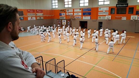 In einer Sporthalle üben Dutzende Karate-Kämpfer im Synchronmuster Schläge und Tritte