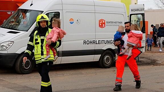 Ein Feuerwehrmann und ein Sanitäter mit kleinen Kindern auf dem Arm