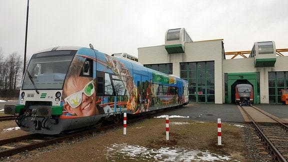 Vor dem Betriebsbahnhof der Vogtlandbahn steht ein bunter Zug