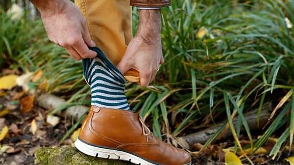 Eine Socke wird über ein Hosenbein gezogen