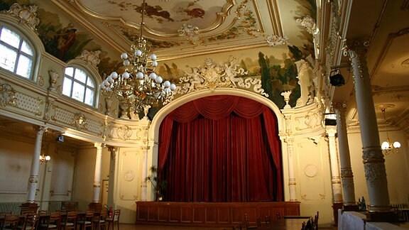 Ein prunkvoller Ballsaal mit aufwenigen Stuckarbeiten an Decke und Wänden und einer großer Bühne mit roten Samtvorhängen