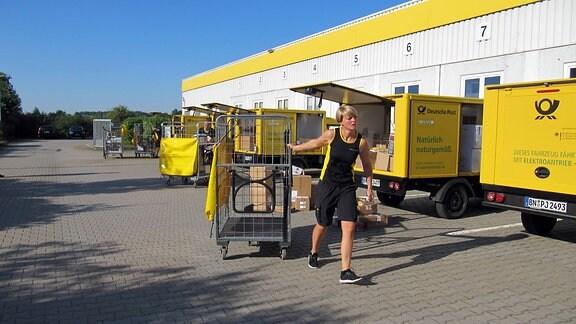 Die kleine Flotte von Streetscootern wird mit Paketen und Briefen beladen