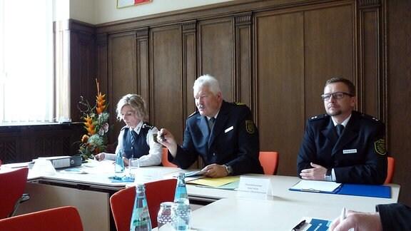 Eine Polizistin und zwei Polizisten sitzen an einem Podium.