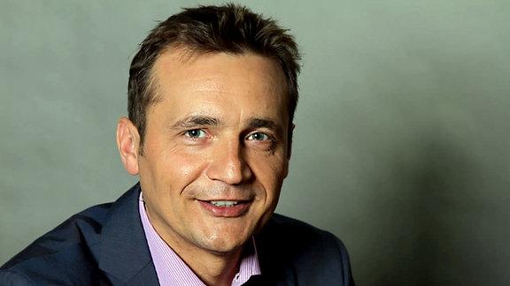 Ein Mann mit blauem Anzug und lila gestreiftem Hemd lächelt freundlich in die Kamera