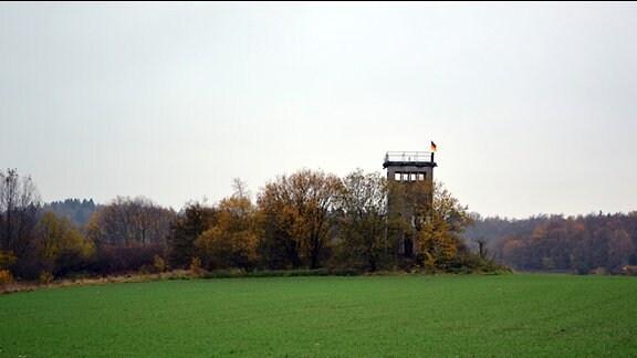Blick über ein Feld auf einen alten Grenzturm