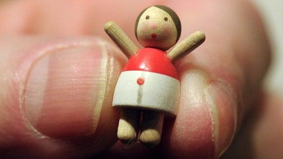 Ein kleines Holzpüppchen wird zwischen zwei Fingern gehalten.