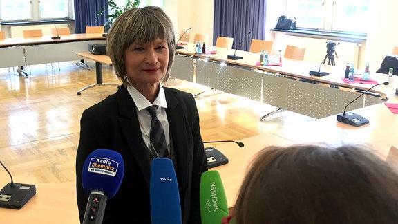 Eine Frau spricht in die Mikrofone von Journalisten