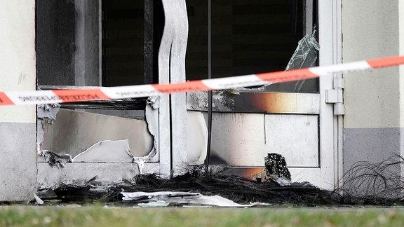 Eine durch Feuer verbogene Eingangstür hinter Polizeiabsperrband