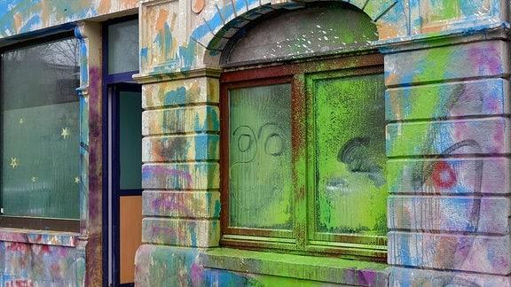 Ein Fenster und eine Hausfassade sind vollständig mit verschiedenen Farben beschmiert