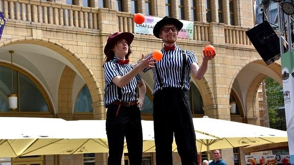 zwei Jongleurkünstler mit orangen Bällen