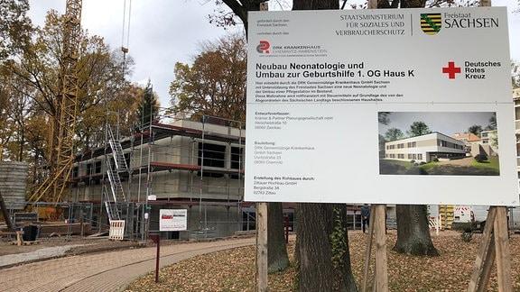 Eine Bautafel mit Erklärung zum Neubau steht vor einem eingerüsteten Rohbau