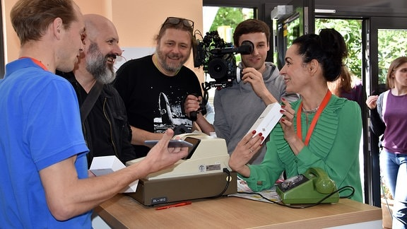 Sukuma Award Chemnitz.jpg: drei Schauspieler und Filmteam beim Dreh in einem Handyladen