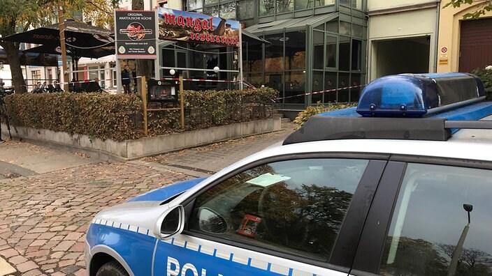 Ein Polizeifahrzeug steht vor einem mit Absperrband gesicherten Biergarten