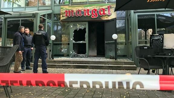Hinter einem Absperrband der Polizei ist die zerstörte Tür eines Restaurants zu sehen