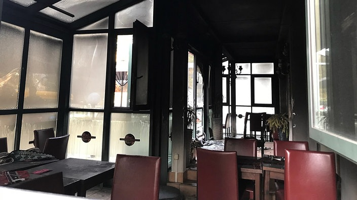 Blick in einen verrussten Wintergarten eines Restaurants mit deutlichen Brandspuren