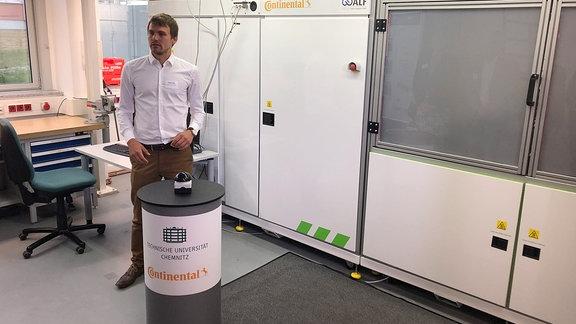 Ein Mann steht vor einer technische Anlage in einer Universität.