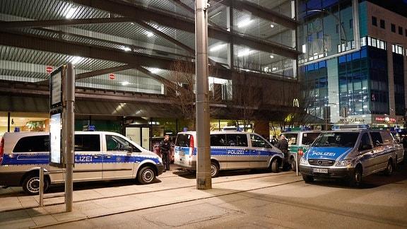 Polizisten und Polizeiautos stehen vor Parkhaus bei Nacht