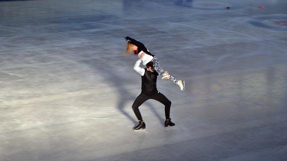Ein Eislaufpaar zeigt eine Hebefigur