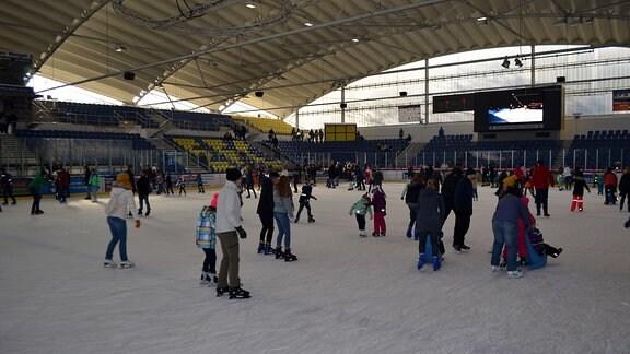 Viele Eisläufer fahren in einer Halle mit Schlittschuhen